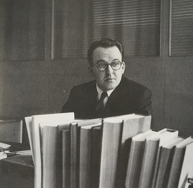 Robert Fulford in suit and tie, with books