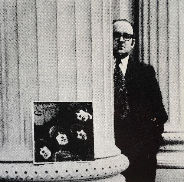 Robert Fulford next to a pillar and album cover for Rubber Soul