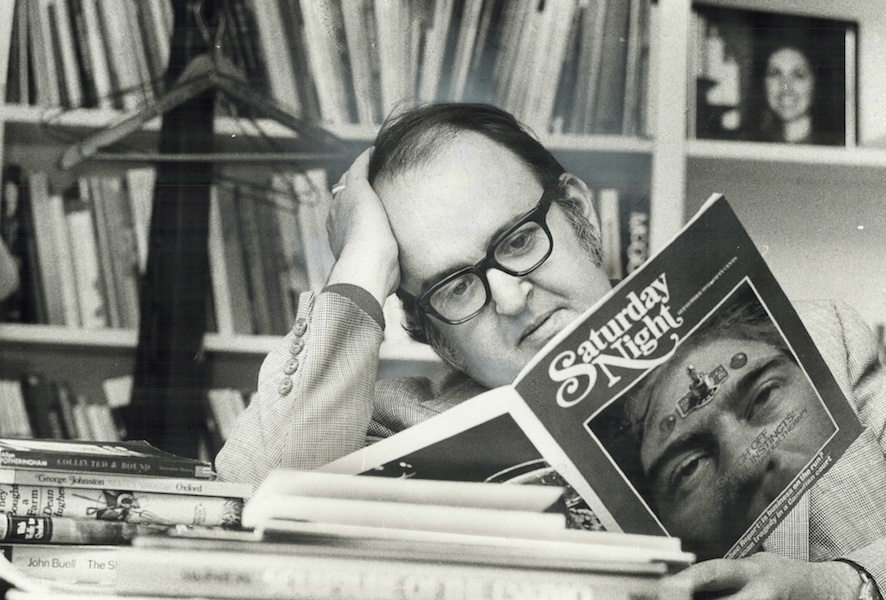 Robert Fulford in his office reading an issue of Saturday Night magazine